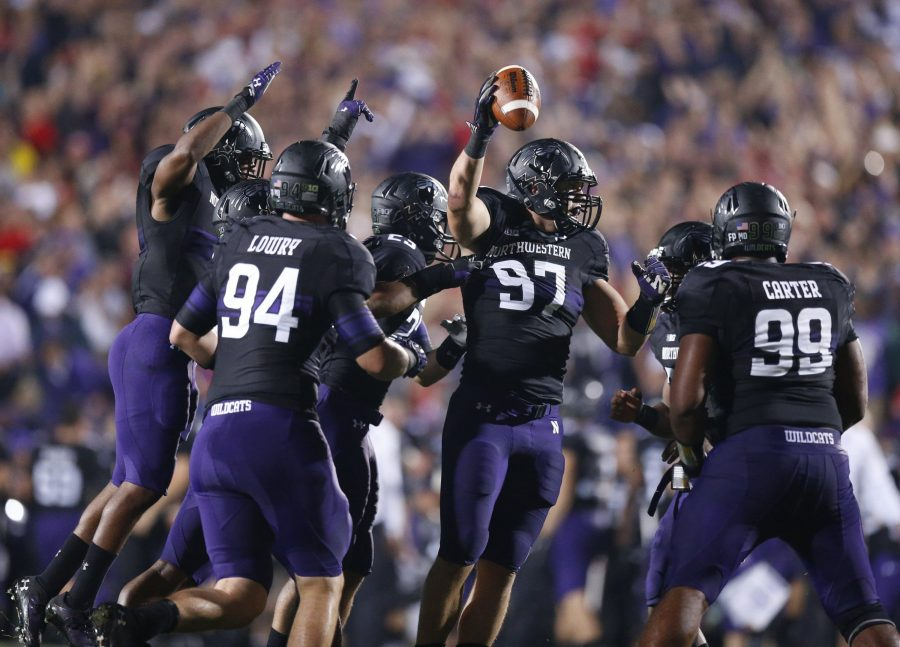 Northwestern defensive players celebrate the recovery of a fumble.(Barbara J. Perenic/Columbus Dispatch/MCT)