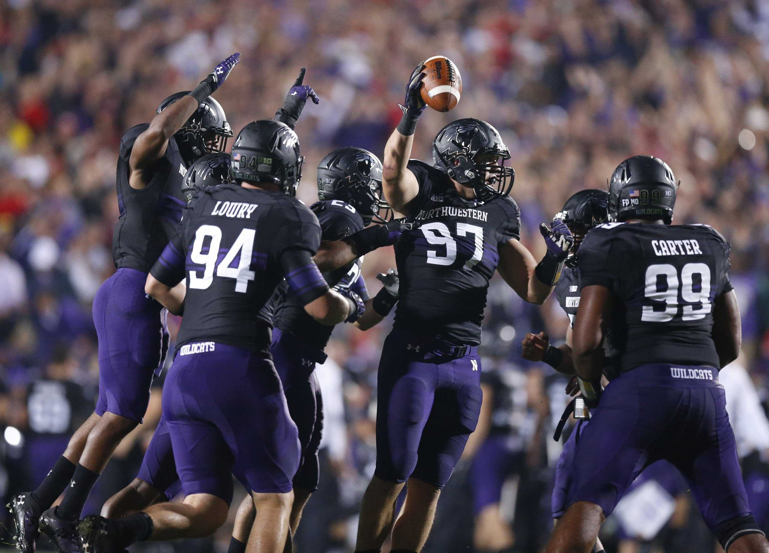 Northwestern defensive players celebrate the recovery of a fumble. (Barbara J. Perenic/Columbus Dispatch/MCT)
