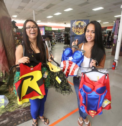 Celeste Contreres, left, and Ashley Dupaya, right, hold the superhero costumes they and a group of women plan to wear for Halloween on Oct. 23, 2014 at Spirit Halloween store in Altamonte Springs, Fla.  Since this year's holiday falls on a Friday, sales are higher than normal. (George Skene/Orlando Sentinel/MCT)