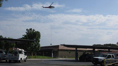 Helicopter transporting HVAC units over rooftops (Martin Chinn)