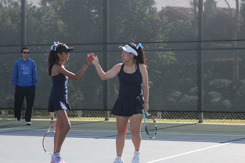 Snigdha Vayalapadu (Jr.) and Kasey Kim (Sr.) high-fiving after receiving a point against Dana Hills. (I.Panis)