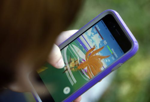 A Pokemon Go player battles the serpent-like creature, Arbok, while walking past the Quetzalcoatl statue in Plaza de Cesar Chavez in San Jose, Calif., on Monday, July 11, 2016. (Karl Mondon/Bay Area News Group/TNS)