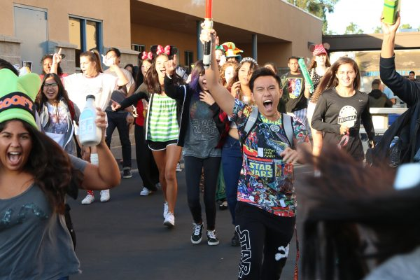 Dress it up Disney: Students dressed as their favorite Disney characters lead a spirit walk Wednesday morning. Alex Tang (Sr.) shouts for spirit! MARTIN CHINN