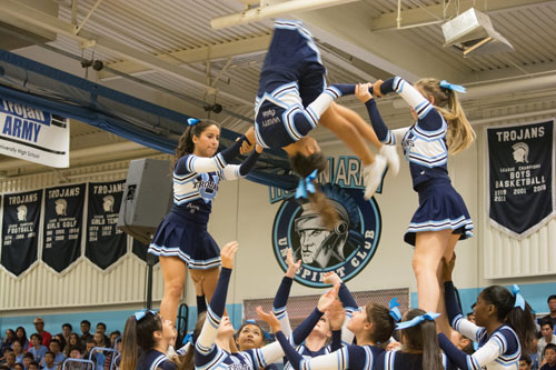 Cheer Captain Serena Wu (Sr.) flips in mid-air, hoisted by Melody Bastani (Jr.) and Kayla Pecanic (Sr.), at the September Pep Assembly.