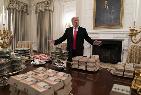 U.S President Donald Trump presents fast food to be served to the Clemson Tigers football team to celebrate their championship at the White House on Jan. 14, 2019 in Washington, D.C. The EPA has curtailed hazardous waste clean-up work, air quality inspections and reviews of toxic substances as a result of Donald Trump's border wall shutdown. (Chris Kleponis/Pool/Getty Images/TNS)