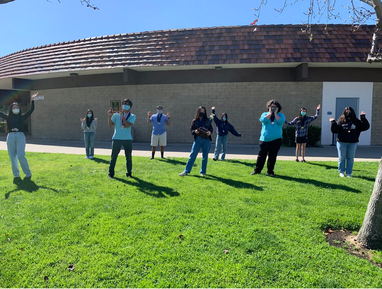 The Academic Decathlon team celebrates their regional competition win on the front lawn of the administration building, abiding by COVID guidelines.