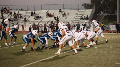 The football team lines up on offense against Oceanview